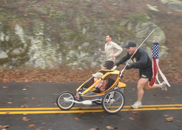 man running with baby stroller